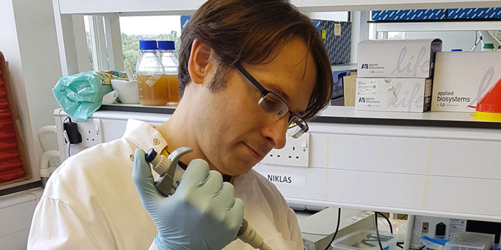 Brown haired man with glasses in lab coat