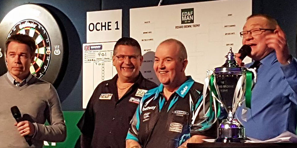 2 darts players on stage with trophy