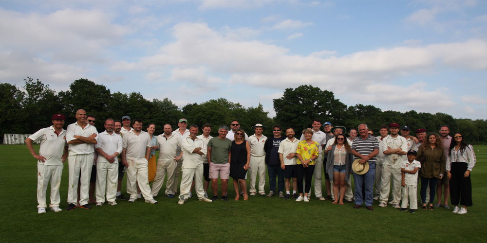 20+ crickters and family stood on grass
